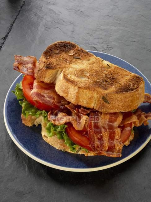 Vista del primo piano di un panino tostato, pancetta, lattuga e pomodoro sulla banda nera — Foto stock