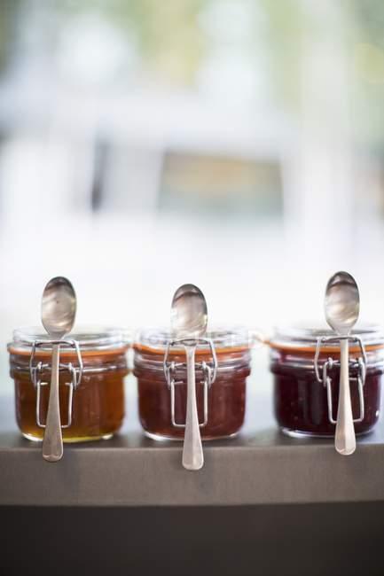 Vasetti di marmellate di frutta con cucchiai — Foto stock