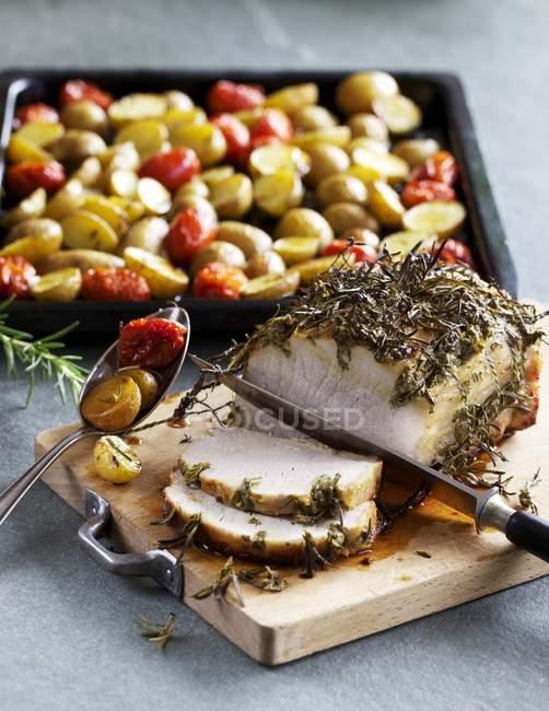 Partly sliced Herb roasted pork — Stock Photo