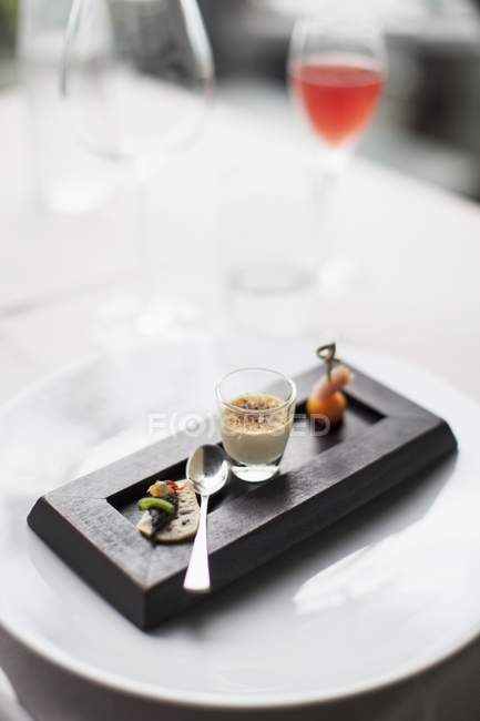 Elevated view of goose Creme brulee with appetizers and spoon on wooden dish — Stock Photo