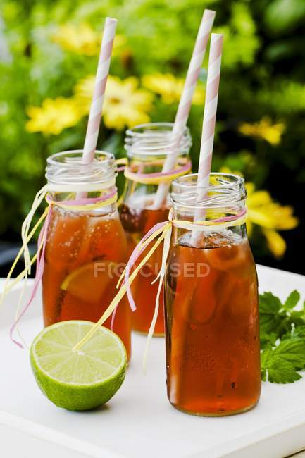 Bottles of iced tea with lime and peppermint — Stock Photo