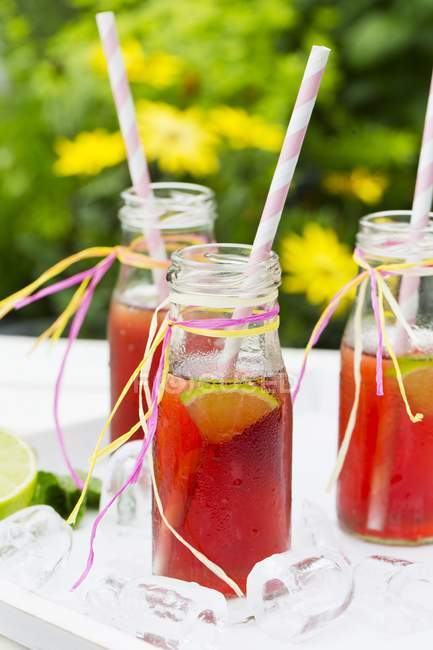 Bottles of iced tea with lime — Stock Photo