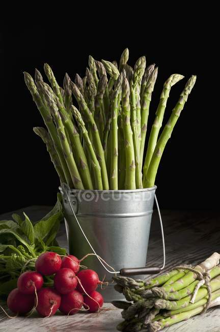 Green asparagus and radishes — Stock Photo
