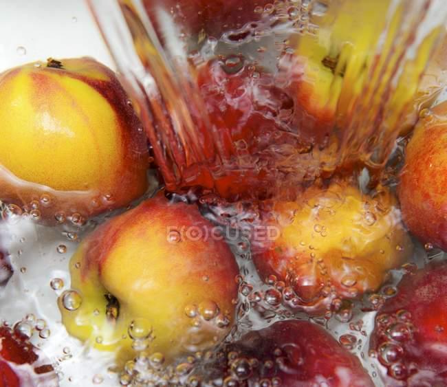 Nectarines in splash of water — Stock Photo