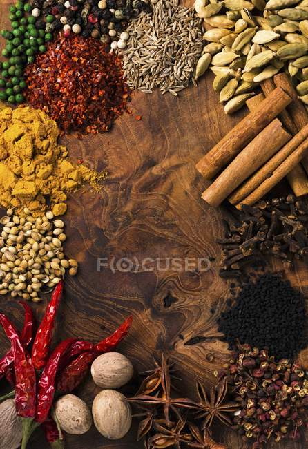 Assorted spices on wooden board — Stock Photo