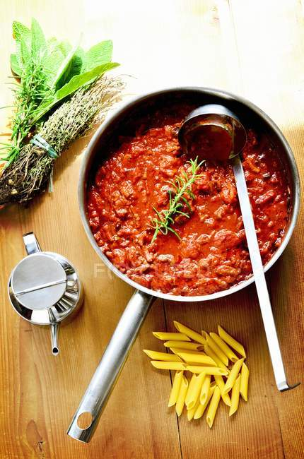 Bolognese sauce in pan near penne pasta — Stock Photo