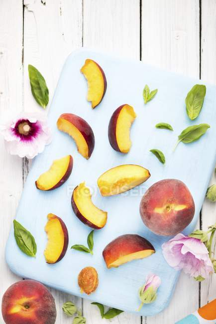 Peaches with slices and flowers — Stock Photo
