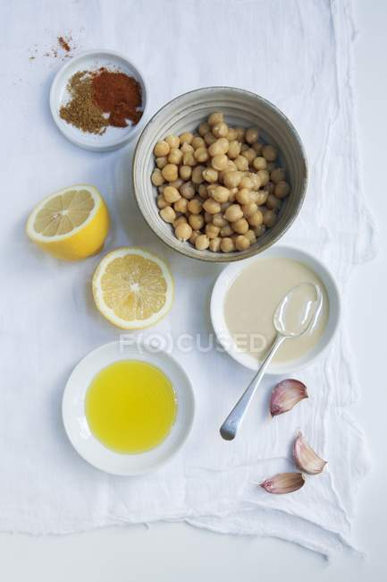 Ingredients for hummus: chickpeas, tahini, garlic, lemon, olive oil, paprika and cumin — Stock Photo