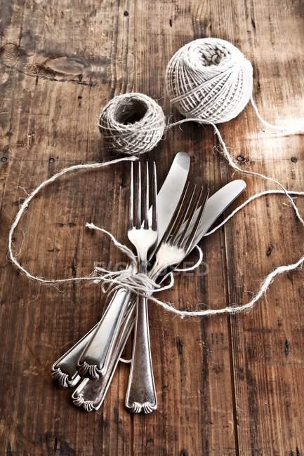Elevado más de un paquete cuchillos y tenedores con cordel de cocina - foto de stock