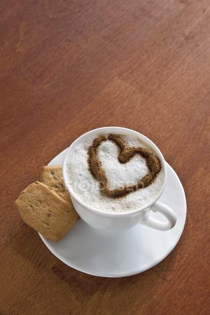 Elevated view of coffee cup decorated with milk foam heart — Stock Photo