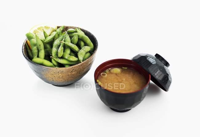 Soupe miso et fèves de soja salées dans des bols sur fond blanc — Photo de stock