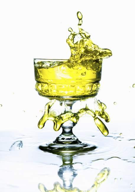 Vue rapprochée d'éclaboussures de boisson jaune d'un verre — Photo de stock