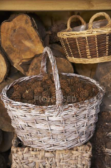 Daytime view of a rustic wicker basket filled with pine cones in front of a wood shed — Stock Photo