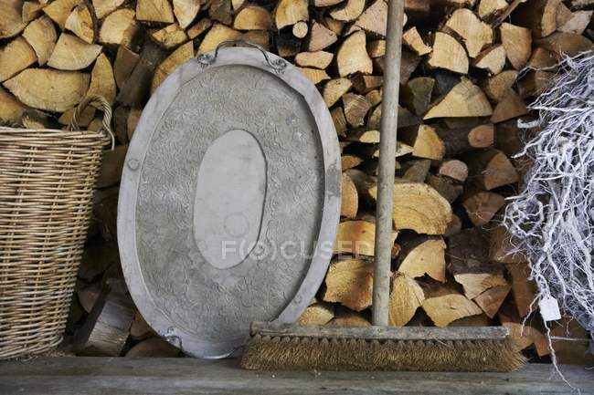 An old broom and a metal tray on a wooden bench in front of a wood pile — Stock Photo