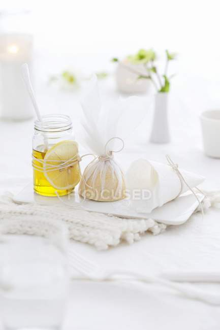 Closeup view of oil and lemons on a laid table — Stock Photo