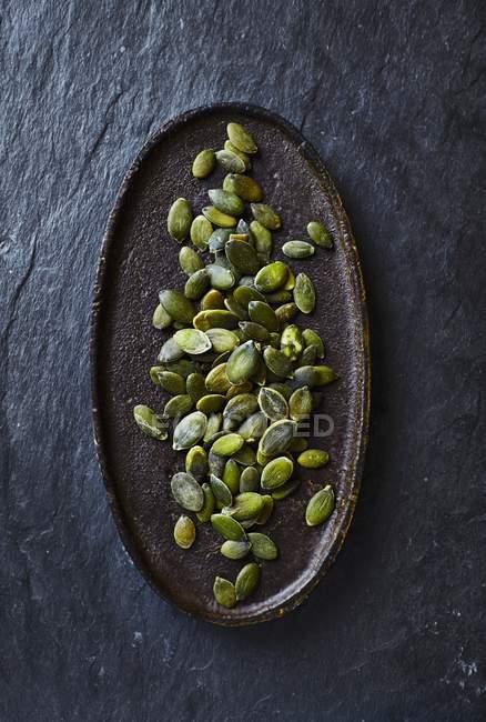Semillas de calabaza en placa oval - foto de stock
