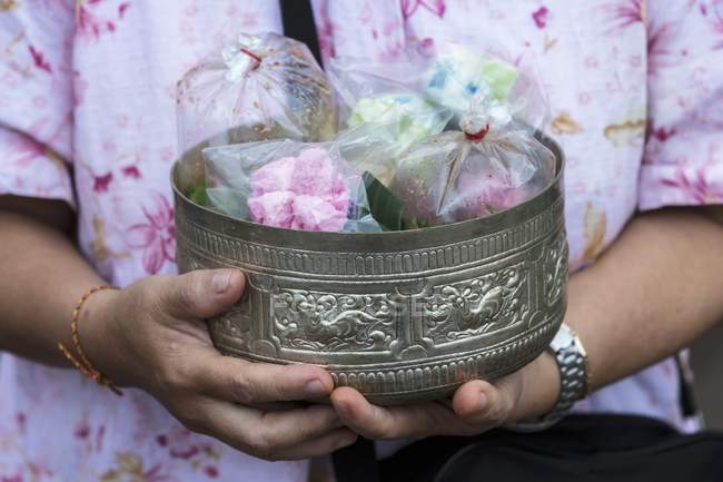 Cropped view of person holding ornate old tin with food bags — Stock Photo