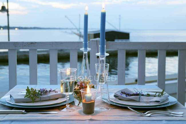 A laid table with candles on a pier at dusk — Stock Photo