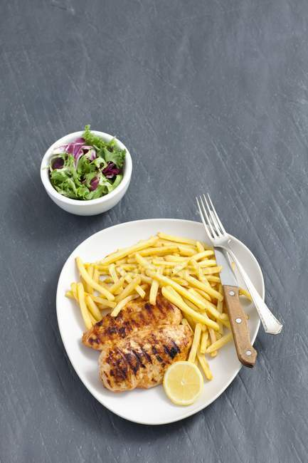 Top view of grilled chicken with French fries, lemon slice and vegetable salad — Stock Photo