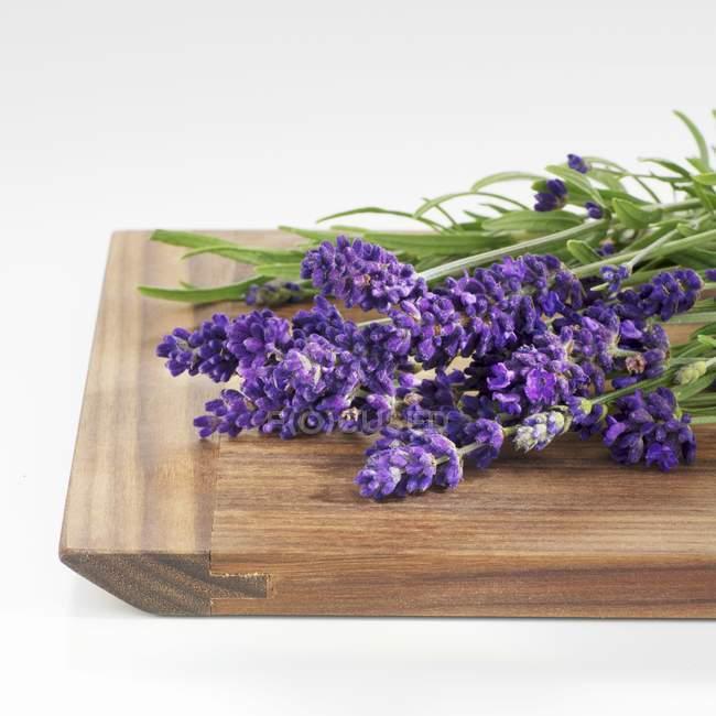 Vista de cerca de las flores de lavanda fresca en una tabla de madera - foto de stock