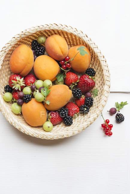 Basket of summer apricots and berries — Stock Photo