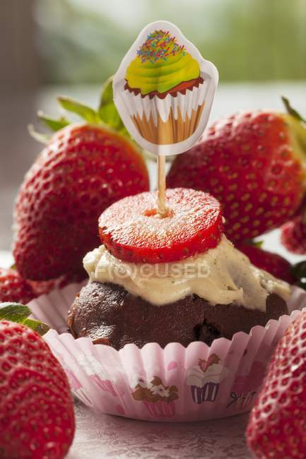 Cupcake with pile of fresh strawberries — Stock Photo