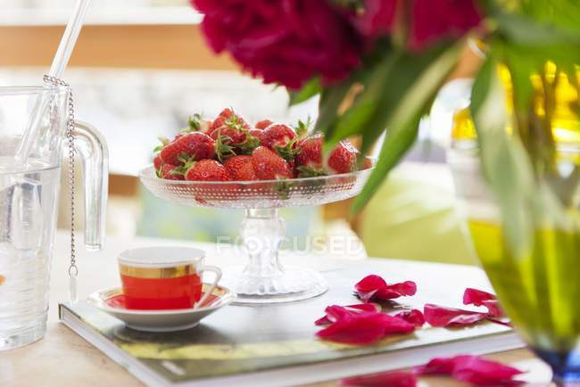 Closeup view of fresh strawberries in glass dish and mocha cup on book with rose petals — Stock Photo