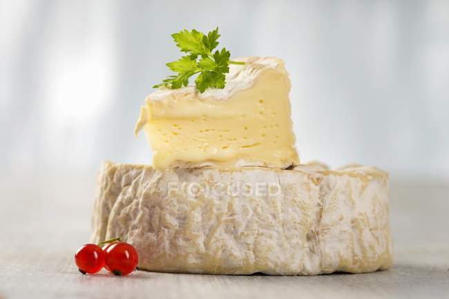 Camembert cheese with slice on top — Stock Photo