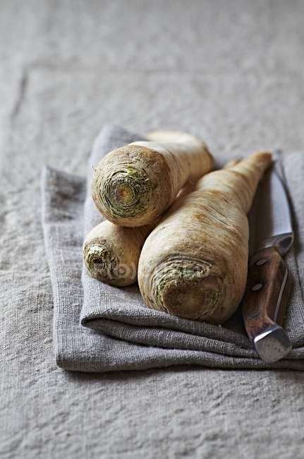 Parsley roots and a kitchen knife — Stock Photo