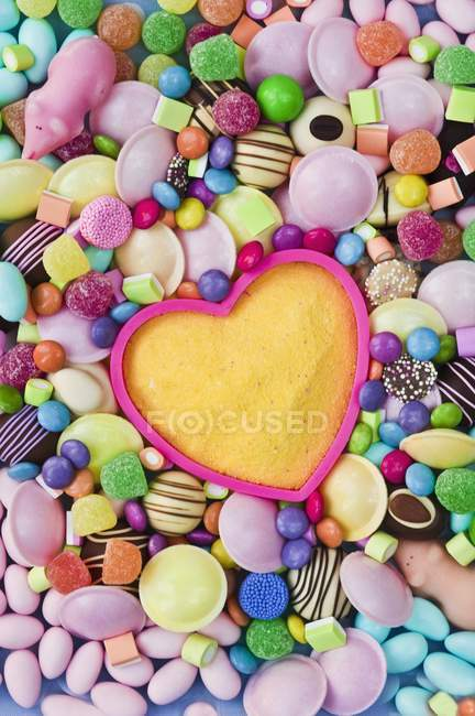 Top view of yellow sugar in baking mould surrounded by different sweets — Stock Photo