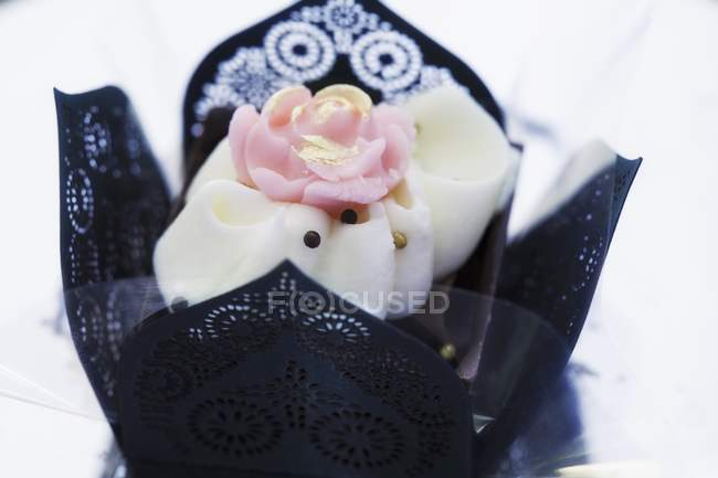 Closeup view of elegant praline decorated with rose in black paper case — Stock Photo