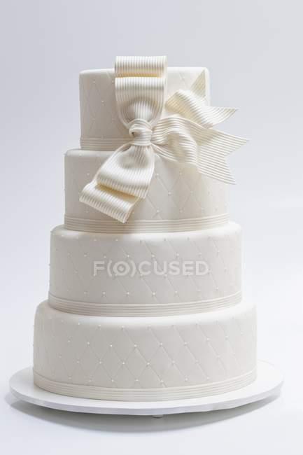 Wedding cake with white bow — Stock Photo