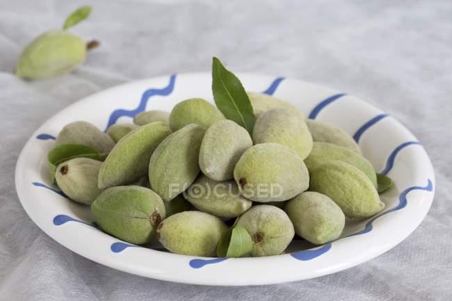 Assiette d'amandes fraîches vertes — Photo de stock