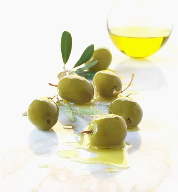 Зеленые оливки и оливковое масло — стоковое фото
