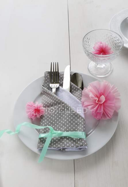 A place setting with a napkin folded as a cutlery bag decorated with paper carnations — Stock Photo