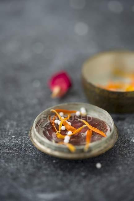 Globuli im Deckel einer alten Dose mit getrockneten Ringelblumenblättern und einem getrockneten Rosenblatt — Stockfoto