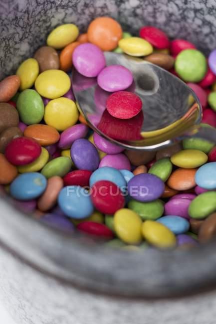 Primo piano vista di fagioli di cioccolato colorati e cucchiaio — Foto stock