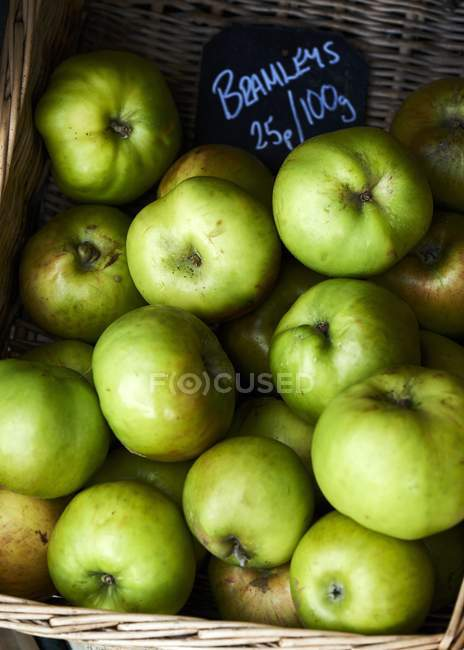 Green Bramley apples with price label — Stock Photo