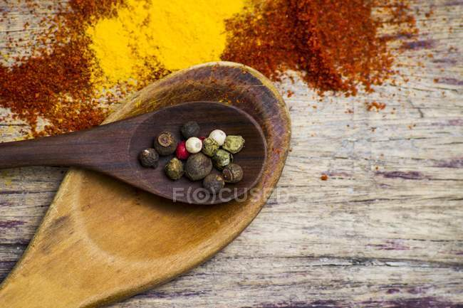 Various colored dried peppercorns on wooden spoons — Stock Photo