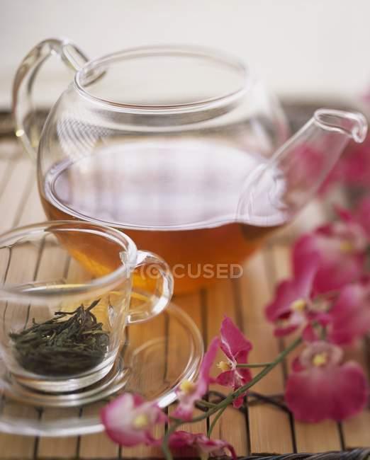 Thé vert dans les feuilles de thé et théière — Photo de stock