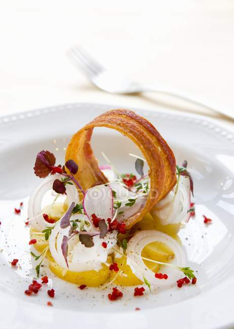 Potatoes with bacon and truffle mayonnaise on white plate — Stock Photo
