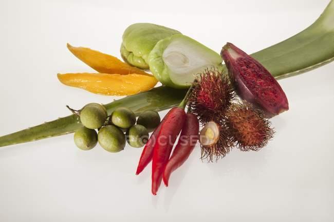 Varios tipos de frutas exóticas y verduras sobre fondo blanco - foto de stock
