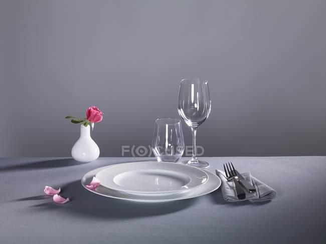 Місце встановлення з тарілки, столові прилади, порожні окуляри і вази квітка на сірий фон — стокове фото