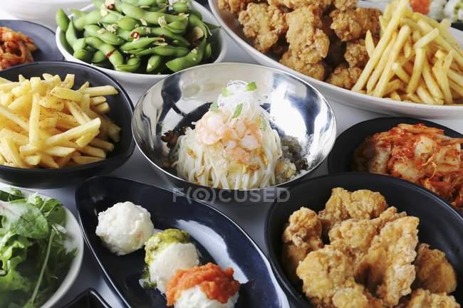 Varios platos de fiesta: frito pollo, soja, patatas fritas y kimchi - foto de stock
