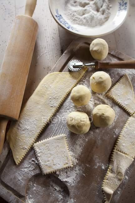 Vista superior da massa de bolinho de massa com farinha, cortador de massa e rolling pin — Fotografia de Stock