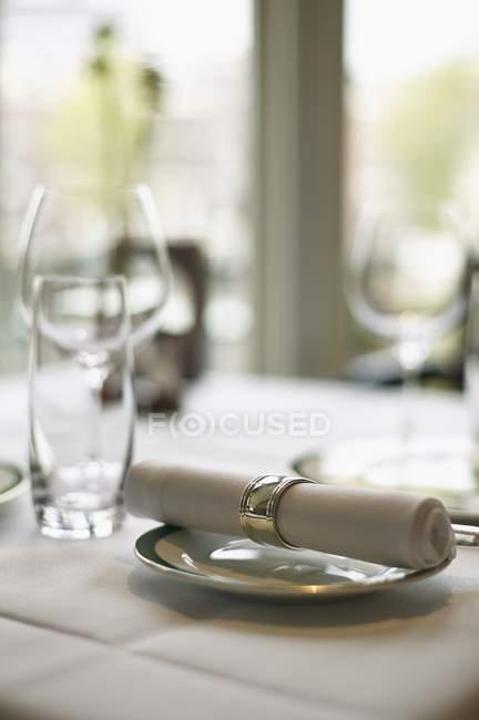 Eine Stoffserviette auf einem Teller und leere Gläser auf einem Tisch in einem Restaurant — Stockfoto