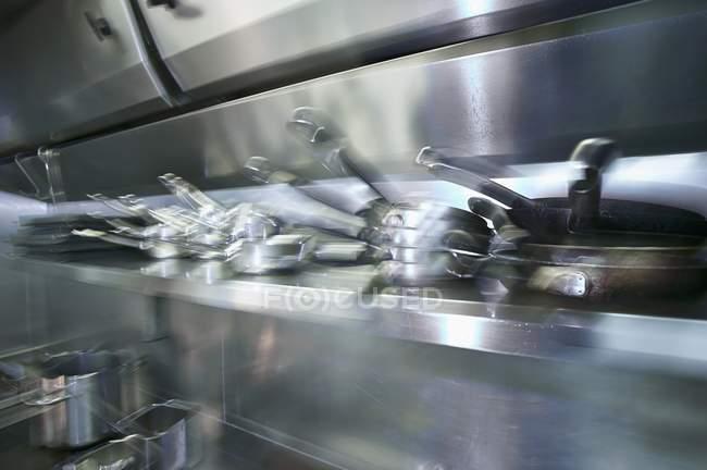 Вид крупным планом размытых кастрюль и сковородки на кухне — стоковое фото