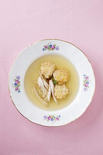 Бульон с фрикадельками и куриными полосками на белой тарелке на розовой поверхности — стоковое фото
