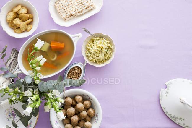 Various dishes for the Jewish festival of Passover over purple surface — Stock Photo