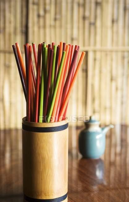 Primo piano vista di bacchette colorate in un contenitore di bambù su un tavolo di legno — Foto stock